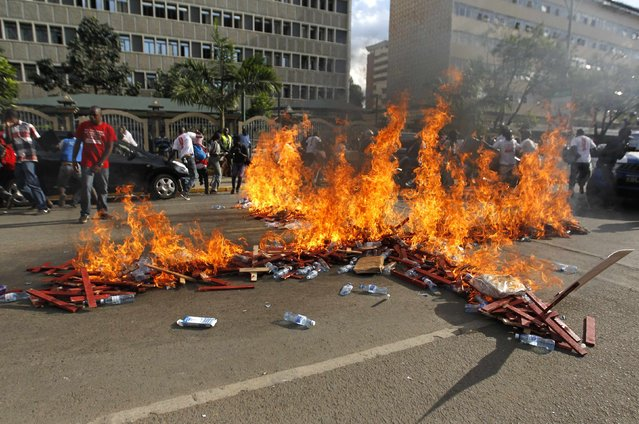 Wooden crosses, symbolising people killed in a series of attacks, are set ablaze by protesters during the #OccupyHarambeeAve demonstration in Kenya's capital Nairobi November 25, 2014. (Photo by Thomas Mukoya/Reuters)