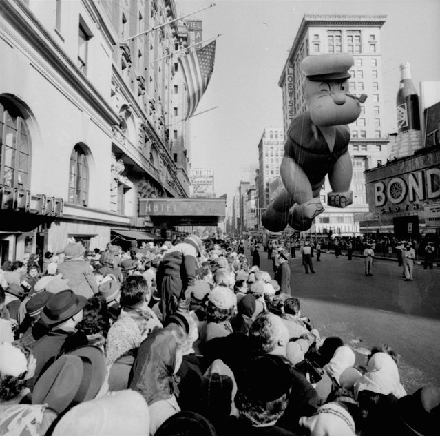 Helium-filled Popeye balloon figure floats above some of the 1,300,000 persons watching the 33rd Macy's Thanksgiving Day Parade pass through Times Square, New York, November 26, 1959. (Photo by AP Photo)