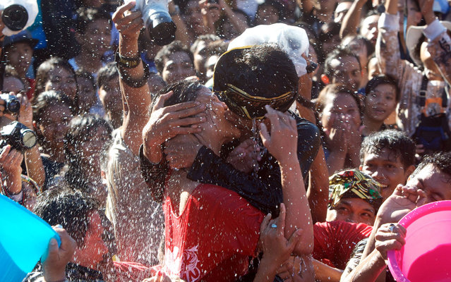 "A young Balinese couple kiss during the Kissing Festival known as ""Omed-Omedan"" at Sesetan village on March 13, 2013 in Denpasar, Bali, Indonesia. During the annual festival, Balinese youths gather first to pray, then to kiss and dance as spectators douse the teenagers with water. The festival follows the Day of Nyepi, and is intended to fend off bad luck in the year ahead. (Photo by Firdia Lisnawati/AP Photo)"