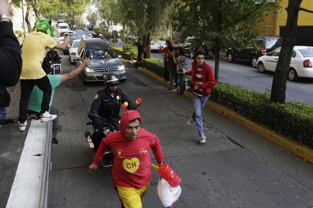 "A man dressed as ""El Chapulin Colorado"", a character by screenwriter Roberto Gomez Bolanos, runs in front of a funeral van carrying the body of Bolanos as they arrive at Mexican media company Televisa in Mexico City November 29, 2014. (Photo by Carlos Jasso/Reuters)"