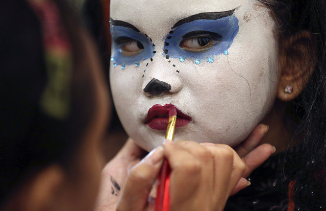 Filipino girl Mikaela Rayll Mangahas has her make-up done as she attends a Halloween event in Manila, Philippines on Sunday, October 25, 2015. (Photo by Aaron Favila/AP Photo)