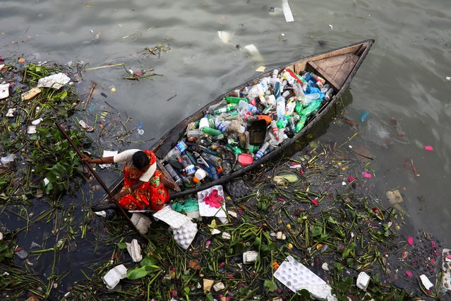 A woman collects plastic waste from the Buriganga river in Dhaka, Bangladesh, September 16, 2020. (Photo by Mohammad Ponir Hossain/Reuters)