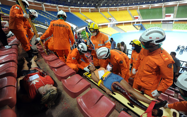 Rescuers participate in an exercise of emergency care of injured fans in football stadiums in Brasilia, on March 20, 2013. Rescuers from several Brazilian states participated in a simulated exercise aimed at the FIFA 2013 Confederations Cup and FIFA 2014 World Cup. (Photo by Evaristo Sá/AFP Photo)
