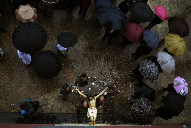 """Spanish legionnaires carry a statue of the Christ of the Mercy into the church after the Palm Sunday procession of the """"Estudiantes"""" brotherhood was suspended due to rain at the start of Holy Week in Oviedo, northern Spain, March 24, 2013. (Photo by Eloy Alonso/Reuters)"""