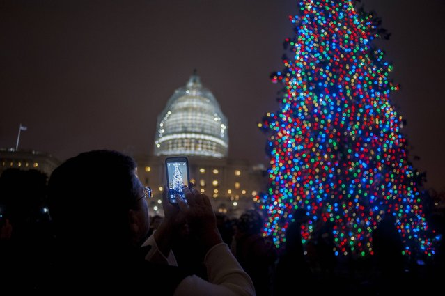 Speaker of the House, John Boehner (R-OH), assisted by Aaron Urban, 10, of Linthicum, MD, threw the switch to light the Capitol Christmas Tree in front of the U.S. Capitol on December 2, 2014 in Washington, DC. Urban, who is fighting brain cancer, is helping light the tree as the kickoff for his one-true-wish, being granted by Make-A-Wish Mid-Atlantic, to spend Christmas in New York City. The tree is an 88-foot white spruce from the Chippewea National Forest in Cass Lake, Minnesota. (Photo by Pete Marovich/Getty Images)