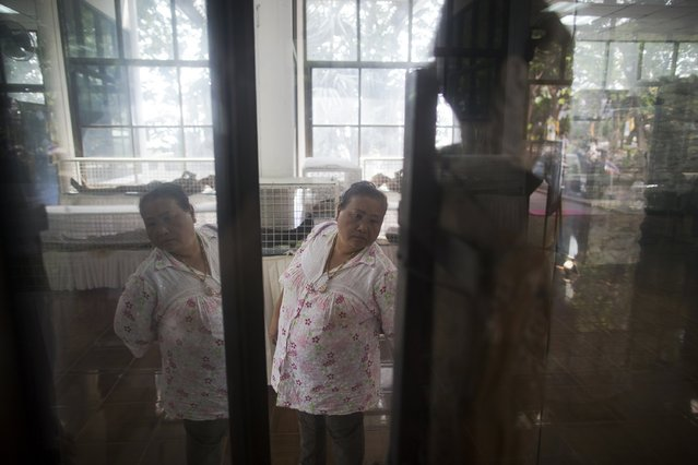 A visitor looks at a preserved body of an AIDS victim is displayed in a museum at the Buddhist temple Wat Prabat Nampu in Lopburi province, north of Bangkok November 30, 2014. (Photo by Damir Sagolj/Reuters)