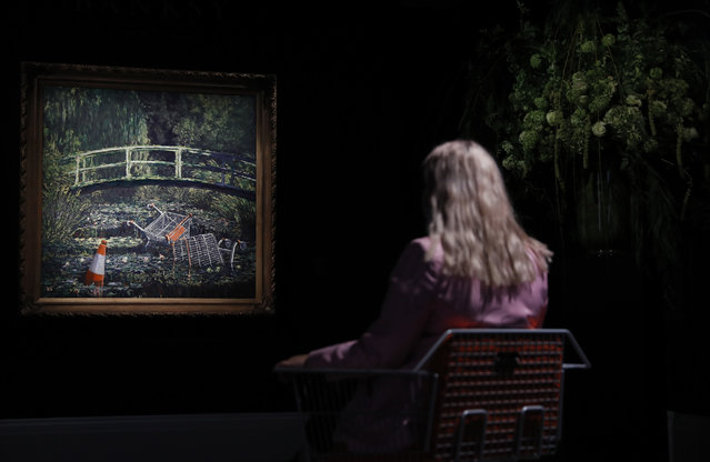 """A member of staff poses in front of a work of art by Banksy entitled """"Show Me The Monet"""" at Sotheby's auction house in London, Friday, October 16, 2020. The painting is valued at 3-5 million pounds (US$ 3.8-6.4 million) when sold at auction on October 21. (Photo by Alastair Grant/AP Photo)"""