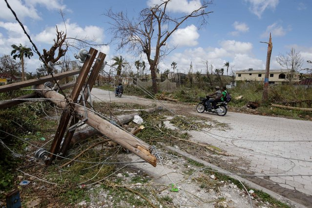 A motorbike passes next to a power line down after Hurricane Matthew in Port Salut, Haiti, October 7, 2016. (Photo by Andres Martinez Casares/Reuters)