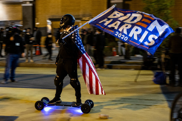 A man with an American flag on his back and a Biden/Harris campaign flag rides an electronic skateboard through Black Lives Matter Plaza in front of the White House on Election Day, November 3, 2020 in Washington, DC. This year's historic presidential election between President Donald Trump, the incumbent, and Democratic nominee Joe Biden begins to come to a close even though final results are not expected for days to come as states take longer to count historic levels of mail-in ballots. (Photo by Samuel Corum/Getty Images)