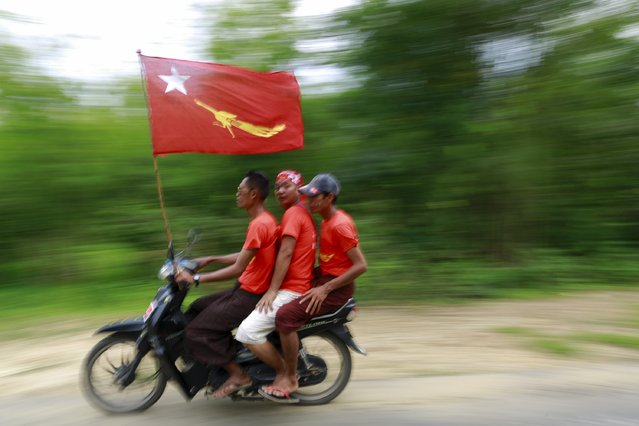 Supporters ride a bike during Myanmar pro-democracy leader Aung San Suu Kyi's campaign rally for the upcoming general elections in her constituency town Kawhmu township, Yangon Division, October 24, 2015. (Photo by Soe Zeya Tun/Reuters)