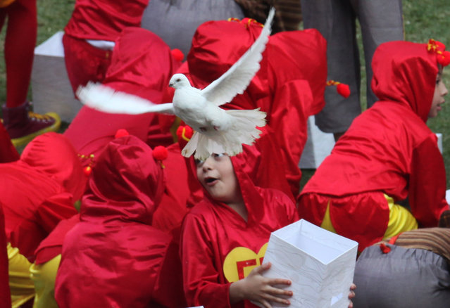 "In this November 30, 2014 file photo, children dressed as ""El Chapulin Colorado"" and ""El Chavo del Ocho"" characters, release white doves during the memorial service of Mexican comedian Roberto Gomez Bolanos at the Azteca stadium the in Mexico City. (Photo by Marco Ugarte/AP Photo)"