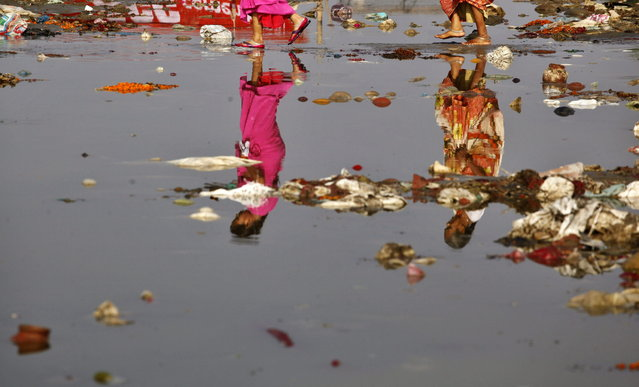 Indian Hindu devotees, reflected on the water, cross the polluted Ganges River at Sangam, the confluence of the Ganges, Yamuna, and the mythical Saraswati River, in Allahabad, India, Monday, April 22, 2013. April 22 is observed as Earth Day every year as a tool to raise ecological awareness. (Photo by Rajesh Kumar Singh/AP Photo)