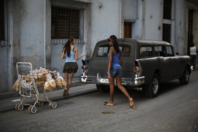 Young women walk in between a shopping cart with baked goods for sale and a vintage car, on a street in Havana December 17, 2014. (Photo by Enrique De La Osa/Reuters)