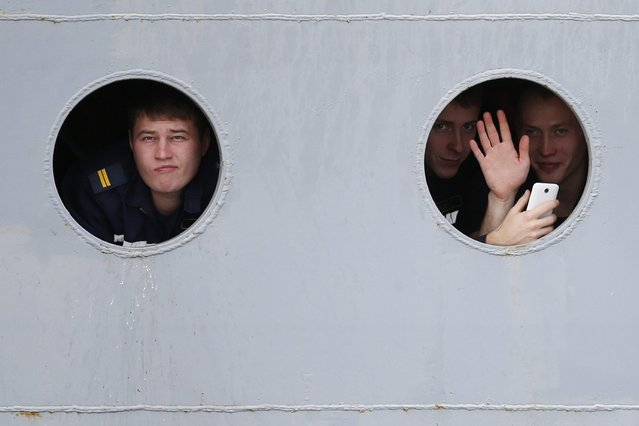 Russian sailors look through the portholes of the Russian Navy frigate Smolny as they leave the STX Les Chantiers de l'Atlantique shipyard site in Saint-Nazaire, western France, December 18, 2014. A ship carrying the Russian sailors, who have been training for months on a French-built Mistral helicopter carrier, left the French port of Saint-Nazaire on Thursday, with it still unclear whether Paris will finally deliver the ship to Moscow. (Photo by Stephane Mahe/Reuters)