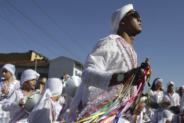 In this October 9, 2016 photo, Matheus Alves, captain of the Mozambique Our Lady of the Rosary dance group, performs during the annual Afro-Christian Congada celebration in Catalao, Goias state, Brazil. His turban is the signature of Mozambique dance group, as they pay tribute to St. Benedict and Our Lady of the Rosary. (Photo by Eraldo Peres/AP Photo)
