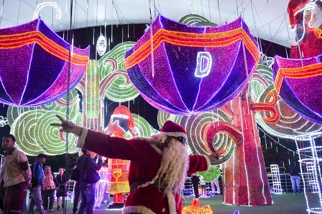 A man dressed as Santa Claus gestures next to the Christmas lights on December 9, 2014 in Medellin, Antioquia department, Colombia. (Photo by Raul Arboleda/AFP Photo)