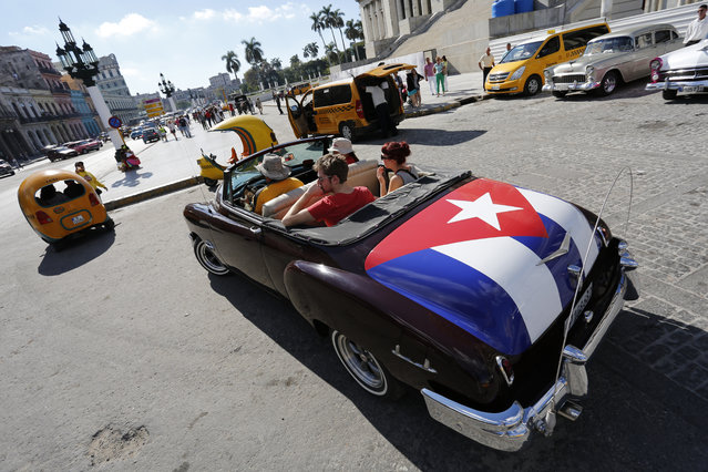In this December 18, 2014 file photo, tourists take a ride in a classic American convertible car with the Cuban national flag painted on the trunk, in Havana, Cuba. American businesses have begun imagining ways to capitalize on last week's announcement that the United States will restore diplomatic ties with Cuba and ease curbs on trade with one of the last surviving communist regimes. (Photo by Desmond Boylan/AP Photo)