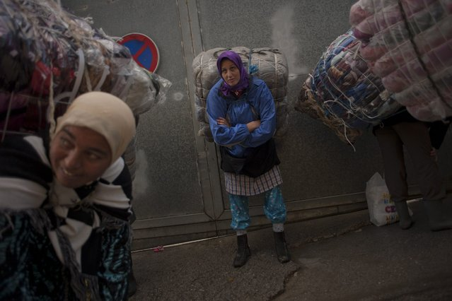 Women porters rest as they carry bundles on their backs for transport across the El Tarajal boarder separating Morocco and Spain's North African enclave of Ceuta, in Ceuta on December 4, 2014. (Photo by Jorge Guerrero/AFP Photo)