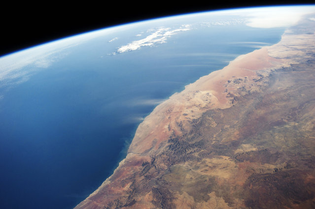 Images of the Namib desert by astronauts on board the International Space Station (ISS) on June 21, 2014 above Namibia. Large dust plumes are visible being carried by strong winds off the coast of the Namib Desert. (Photo by NASA/SPL/Barcroft Media)