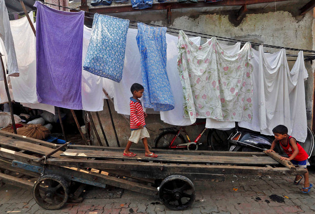 Children play on a hand cart inside a slum in Mumbai, India October 18, 2016. (Photo by Shailesh Andrade/Reuters)