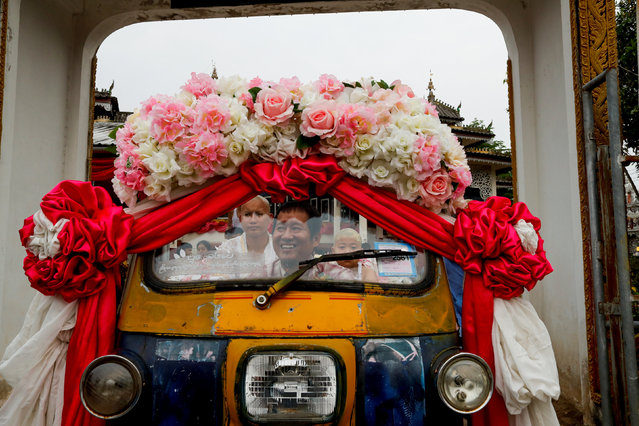 Mr. Kasem rides a tuk-tuk carrying his new ordained sons Apiwvit and Phusit after their heads were shaved at Wat Klang Thung temple in preparation for an annual Poy Sang Long celebration, part of the traditional rite of passage for boys to be initiated as Buddhist novices, in Mae Hong Son, Thailand, April 2, 2018. (Photo by Jorge Silva/Reuters)
