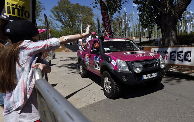 A woman waves as Catherine Houles and co-pilot Sandrine Ridet drive their D-Max Isuzu outside the technical verification area ahead of the Dakar Rally 2015 in Buenos Aires January 2, 2015. (Photo by Marcos Brindicci/Reuters)