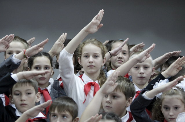 Children, wearing red neckerchiefs, a symbol of the Pioneer Organization, salute while posing for a picture during a ceremony for the inauguration of 18 newly adopted members at a local school in the southern settlement of Kazminskoye in Stavropol region, Russia, November 19, 2015. (Photo by Eduard Korniyenko/Reuters)