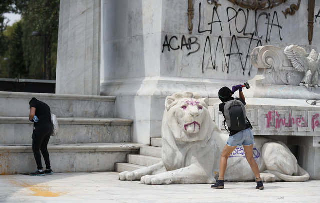 """Protestors angry at the police attack the monument to Mexico's first indigenous president, Benito Juárez, at the Alameda Central park as they destroy storefronts and bus stops in Mexico City, Monday, June 8, 2020. The graffiti reads in Spanish """"The police kill"""". Following the death of Mexican man Giovanni Lopez, who was allegedly beaten to death while in police custody in Jalisco in May, anarchist protesters who are known for their violent tactics smashed storefronts, looted businesses, and sprayed anti-police graffiti on monuments. (Photo by Rebecca Blackwell/AP Photo)"""