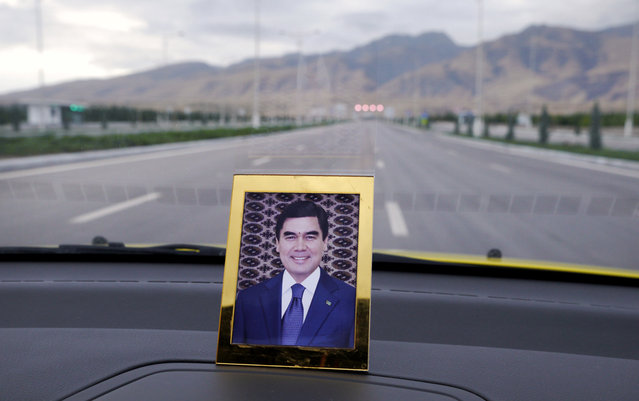 """A portrait of the current president Gurbanguly Berdimuhamedow on a dashboard of a taxi. The former dentist took over the presidency after the death of Niyazov in 2006. Most of the bizarre excesses of his predecessor were swiftly rolled back, but on civil liberties and human rights, he's in less of a rush, telling a reporter """"never run to where you can simply walk"""". (Photo by Amos Chapple via The Atlantic)"""