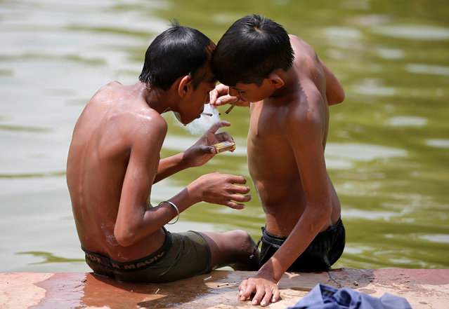 Boys smoke bidi, a local cigarette hand-rolled with tobacco leaf, after taking a dip in a pond to cool off on a hot summer day in New Delhi, India, May 31, 2018. (Photo by Amit Dave/Reuters)