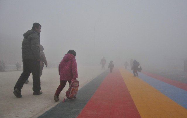 Parents walk primary school students to school amid thick haze in Chiping county, Shandong province January 16, 2015. The National Meteorological Center of China Meteorological Administration (CMA) issued a yellow smog alert early on Wednesday, predicting that smog will persist in most parts of the country for the upcoming days, Xinhua News Agency reported. (Photo by Reuters/China Daily)