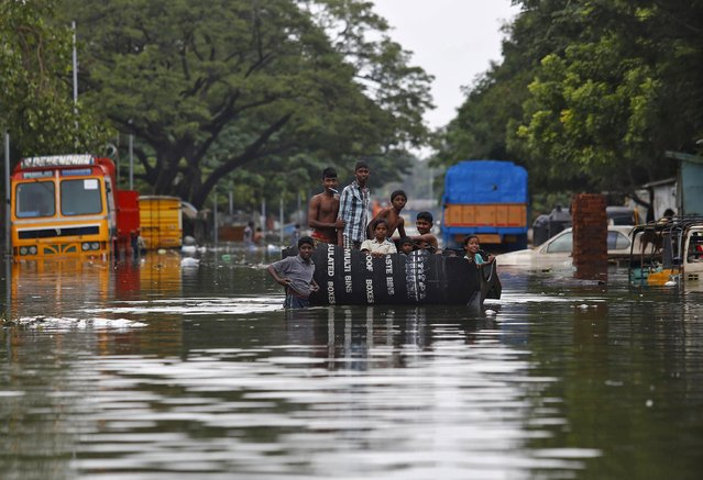 Flood-affected people use a piece of a plastic water tank as they make their way to the market to buy food items in a flooded locality in Chennai, India, December 5, 2015. (Photo by Anindito Mukherjee/Reuters)