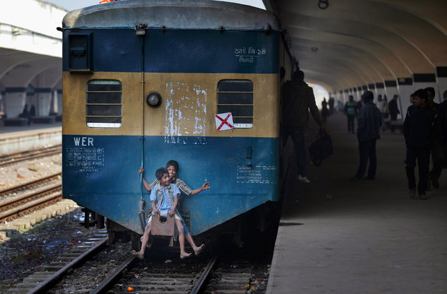 Bangladeshi children travel at the back side of a moving train at a railway station during the second day of a 48-hour general strike called by the opposition Bangladesh Nationalist Party (BNP) in Dhaka, Bangladesh, Thursday, January 22, 2015. Supporters of former Prime Minister Khaleda Zia. (Photo by A. M. Ahad/AP Photo)
