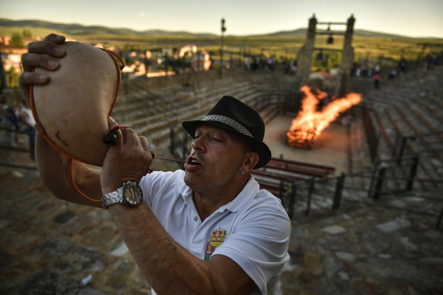 A man drinks from wineskin before walking on the burning embers during the night of San Juan in San Pedro Manrique, northern Spain, Saturday, June 23, 2018. The night of San Juan, which welcomes the summer season, is an ancient tradition celebrated every year in various towns in Spain. (Photo by Alvaro Barrientos/AP Photo)