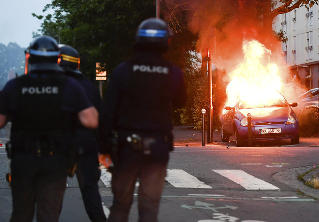 Police officers watch a car burning in Nantes, western France, Tuesday July 3, 2018. French authorities called for calm in France's western city of Nantes after scuffles with police broke out overnight, after police shot at a young driver who was trying to avoid a control. (Photo by Franck Dubray/AP Photo)