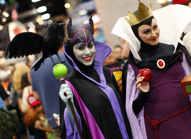 """Attendees dressed as villains Maleficent from """"Sleeping Beauty"""" (L) and The Evil Queen Grimhilde from """"Snow White"""" walk the convention floor at Comic Con in San Diego, California, in this July 21, 2011 file photo. (Photo by Mike Blake/Reuters)"""