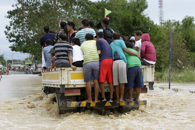 People ride on a delivery truck to cross a flooded road after heavy rain at Candaba town, Pampanga province, north of Manila, December 17, 2015. (Photo by Czar Dancel/Reuters)
