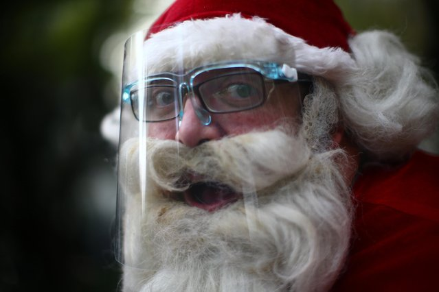 """Alejandro Zelayaran, 43, dressed as Santa Claus, wears a protective face shield as he poses for a photograph on a street in Mexico City, Mexico, December 3, 2020. """"Faith and hope must move the heart of the humanity"""", said Zelayaran, who will don a face shield when he distributes dolls and other gifts at an orphanage in Mexico City. """"I want to see families taking care of each other and knowing that even from afar, love and hope always survive"""". (Photo by Edgard Garrido/Reuters)"""