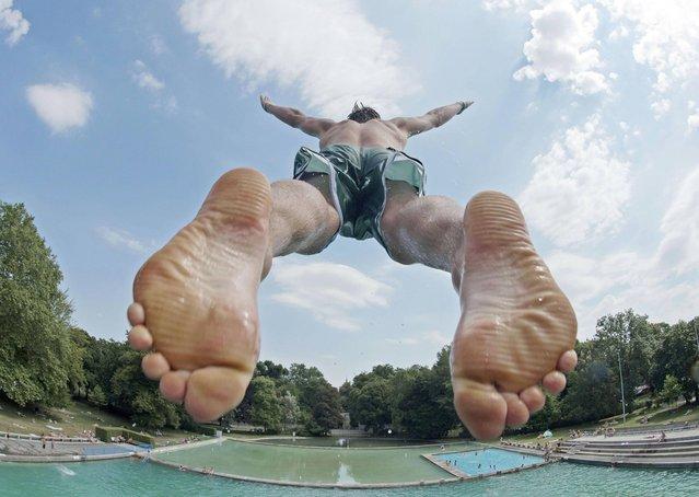 "A boy jumps from a diving platform in the cool water of the swimming pool ""Schwanseebad"" in Weimar, Germany, Tuesday, July 23, 2013. Meteorologists forecast the hot and sunny weather to continue in Germany. (Photo by Jens Meyer/AP Photo)"