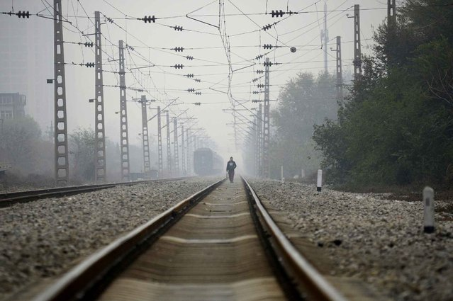 A man walks along a train track in Beijing on November 10, 2016. (Photo by Wang Zhao/AFP Photo)