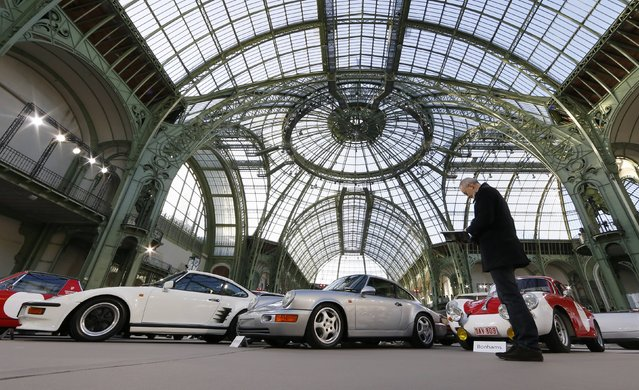 A visitor looks at vintage and classic cars displayed ahead of the Bonhams' Les Grandes Marques du Monde vintage motor cars and motorcycles auction at the Grand Palais exhibition hall as part of the Retromobile vintage car show in Paris February 4, 2015. (Photo by Gonzalo Fuentes/Reuters)