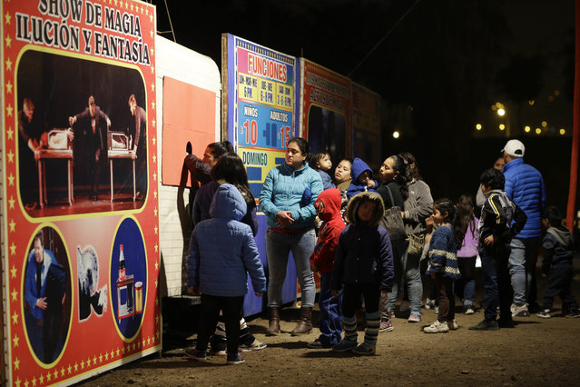 """In this July 20, 2018 photo, people buy tickets to enter a show by the International Circus set up in the shantytown of Pro on the outskirts of Lima, Peru. The billboard at left reads in Spanish """"Magic, illusion and fantasy show"""". (Photo by Martin Mejia/AP Photo)"""