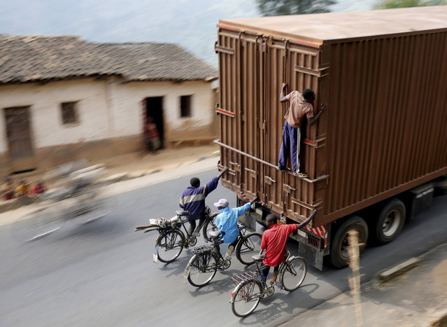 Cyclists hang on to the back of a truck outside the capital Bujumbura, July 19, 2015, as the country awaits next week's presidential elections. Each day scores of cyclists make the 45 kilometer (27 miles) downhill journey at breakneck speed from Bugarama to sell bananas, often hanging from the back of trucks for the return uphill trip. (Photo by Mike Hutchings/Reuters)