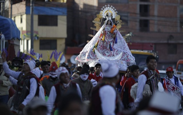 In this Sunday, August 5, 2018 photo, faithful take part in a religious procession honoring Our Lady of Copacabana, in Cuzco, Peru. The veneration of Bolivia's patron saint in Cuzco began a decade ago with a small feast among friends and family. Now an annual event, it has grown in popularity with as many as 500 people taking part. (Photo by Martin Mejia/AP Photo)