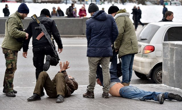 A patrol made up of members of a Ukrainian volunteers battalion and policemen arrest two men on Independence Square in Kiev on February 9, 2015, who allegedly arrived from Donetsk and are suspected of participating in seperatist activities and organizing terrorist attacks in the Ukrainian capital. (Photo by Sergei Supinsky/AFP Photo)