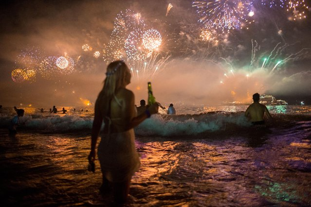 Fireworks light the sky over Copacabana beach during New Year's Eve celebrations in Rio de Janeiro, Brazil, Thursday, January 1, 2016. (Photo by Mauro Pimentel/AP Photo)
