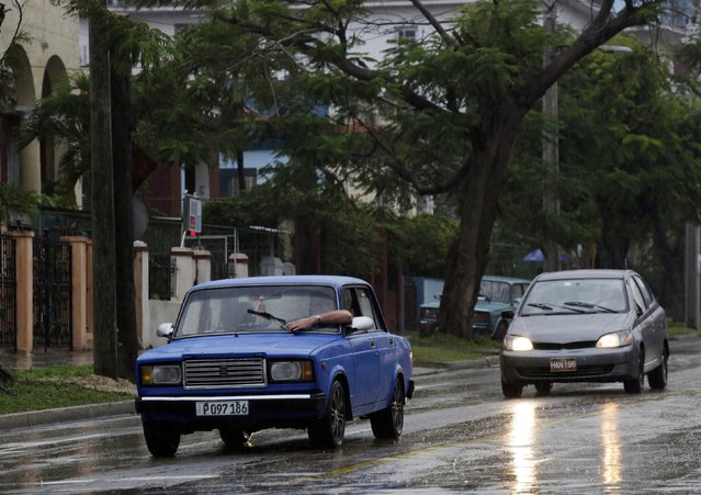 A man tries to adjust the windshield wiper of his Lada while driving in the rain in Havana February 8, 2015. (Photo by Enrique De La Osa/Reuters)