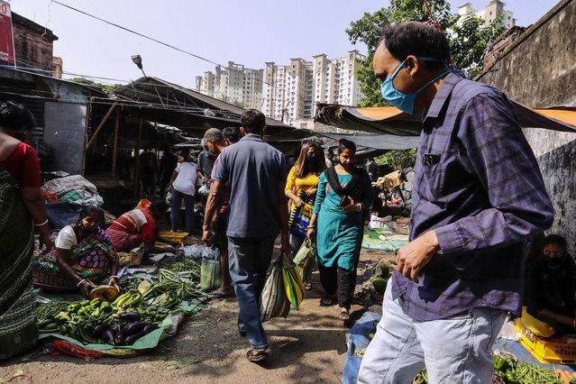 People wearing face mask as a precautionary measure against the coronavirus buy vegetables inside a narrow alley in Kolkata, India, Sunday, November 22, 2020. (Photo by Bikas Das/AP Photo)