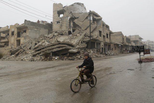 A boy rides a bicycle past damaged buildings in the rebel-controlled area of Maaret al-Numan town in Idlib province, Syria, January 4, 2016. (Photo by Khalil Ashawi/Reuters)