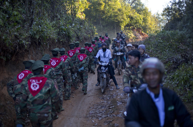 In this January 12, 2015 photo, men on motorcycles watch officers of the Ta'ang National Liberation army, who gathered in the steep, mountainside village of Mar Wong in northern Shan state, Myanmar to celebrate the 52nd anniversary of their insurrection against successive governments. (Photo by Gemunu Amarasinghe/AP Photo)